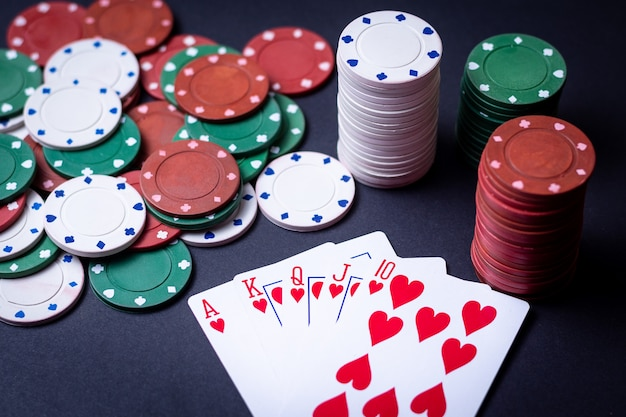 Hand of royal flush playing cards with poker chips
