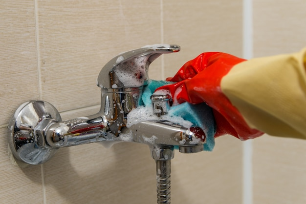 Hand in rubber glove cleans dirty calcified shower mixer tap, close up photo