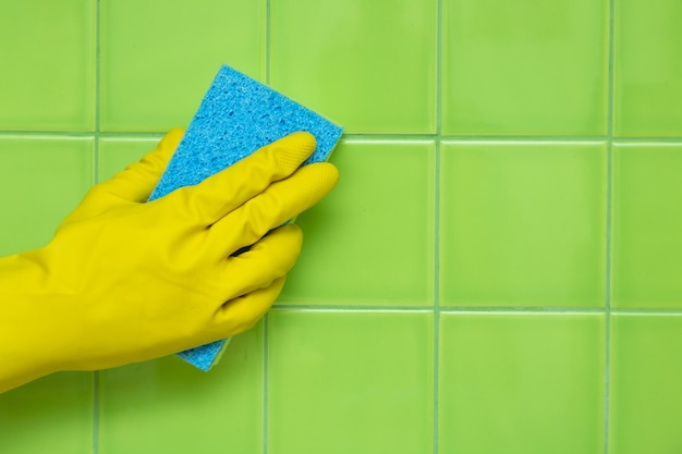 Hand in rubber glove holding an yellow sponge and cleaning tiles