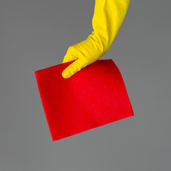 A hand in a rubber glove holds a bright microfiber duster cleaning.