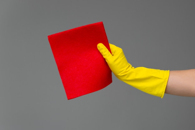 A hand in a rubber glove holds a bright microfiber duster on a neutral background