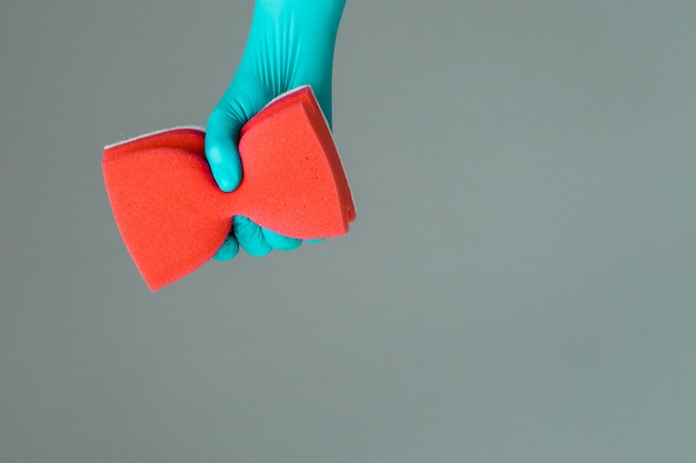 Hand in rubber glove holds color wash sponge. the concept of bright spring, spring cleaning.