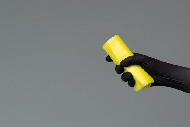 Hand in rubber glove holds colored garbage bag on neutral background
