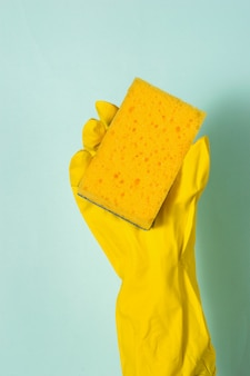 A hand in a rubber glove holds a foam sponge on a blue surface