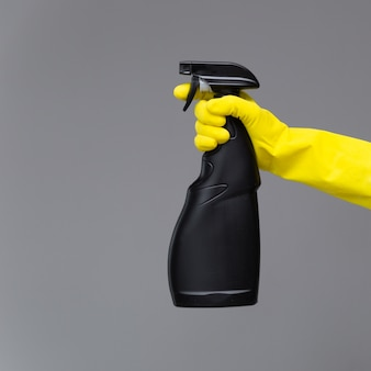 A hand in a rubber glove holds the glass cleaner in a spray bottle