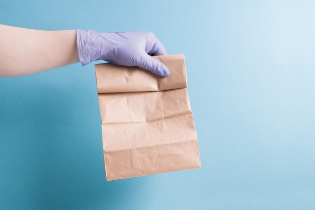 Hand in a rubber glove holds a paper bag on a blue background, copy space