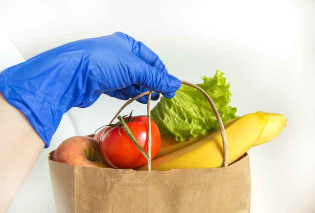 A hand in a rubber glove holds a paper bag with vegetables and fruits, food delivery in eco-friendly packaging, zero waste