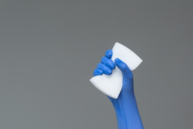 Hand in rubber glove holds wash sponge on grey