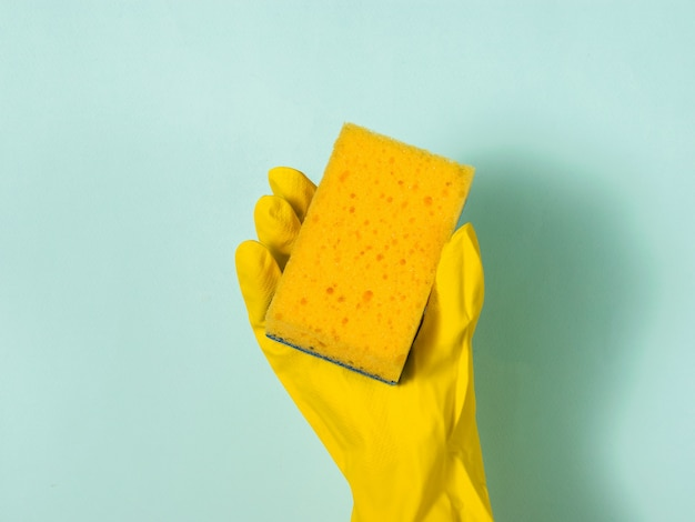A hand in a rubber glove holds a yellow foam sponge on blue. homework. washing dishes by hand.
