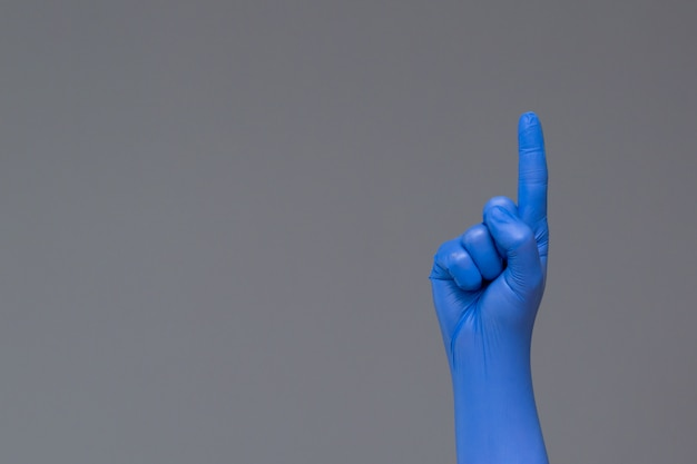 Hand in rubber glove points upwards with index finger, copyspace.