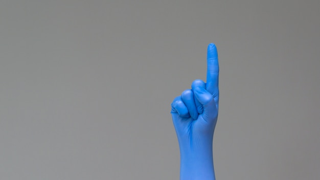 Hand in rubber glove points upwards with index finger.