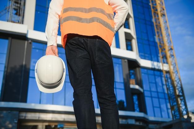 현장 배경에 건물과 함께 안전 헬멧을 들고 손의 엔지니어 작업자.