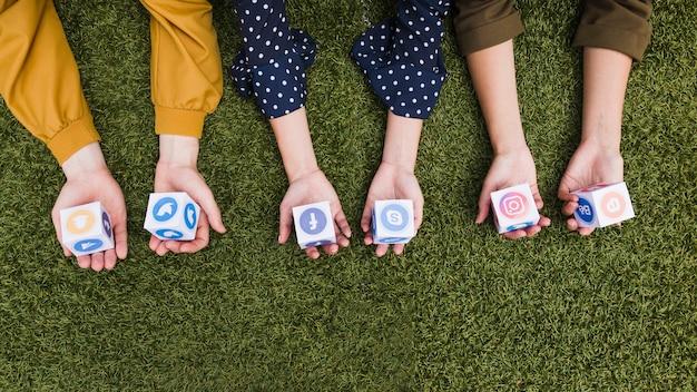 Hand's holding social media app icons blocks on green grass