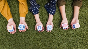 Hand's holding social media app icons blocks on green grass