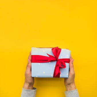 Hand's holding wrapped gift box with red ribbon bow over yellow background