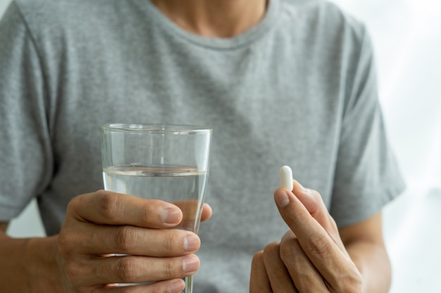 식이 보충제 또는 약물 또는 비타민과 복용 준비가 된 물 한 잔을 들고 손의 남자. 의료, 의학, 셀프 케어, 질병 및 약국 개념.