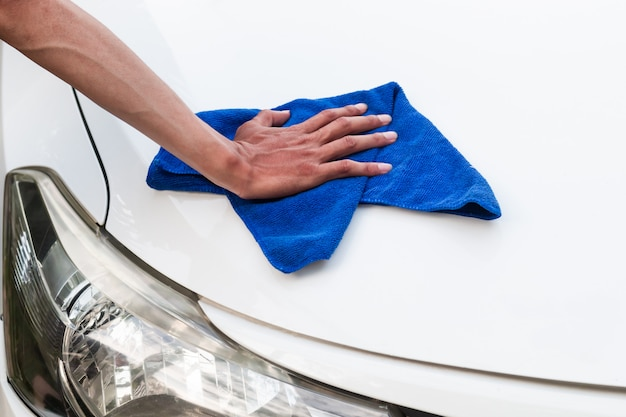 Hand's man with microfiber cloth polishing car