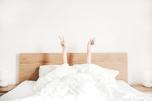 흰색 리넨과 함께 침대에서 커피 잔과 젊은 여자의 손