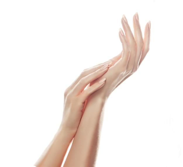 手のスキンケア。爪に淡いピンクのマニキュアと美しい女性の手。