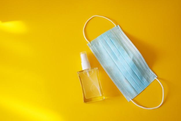 Дезинфицирующее средство для рук и медицинская защитная маска на желтом столе