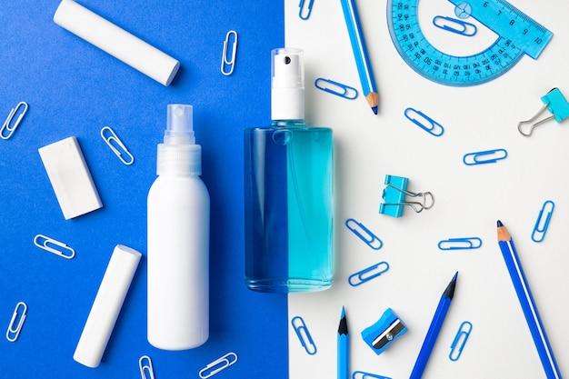 Дезинфицирующее средство для рук и школьные принадлежности, такие как мелки, скрепки на синей и белой бумаге.