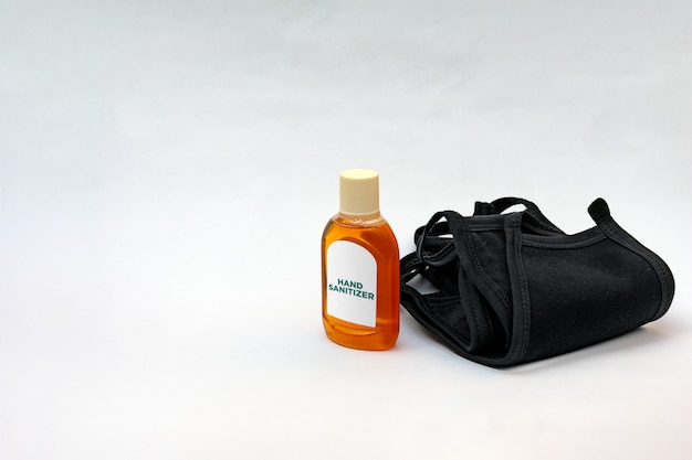 Hand sanitizer bottle and black medical face masks isolated on white background with copy space