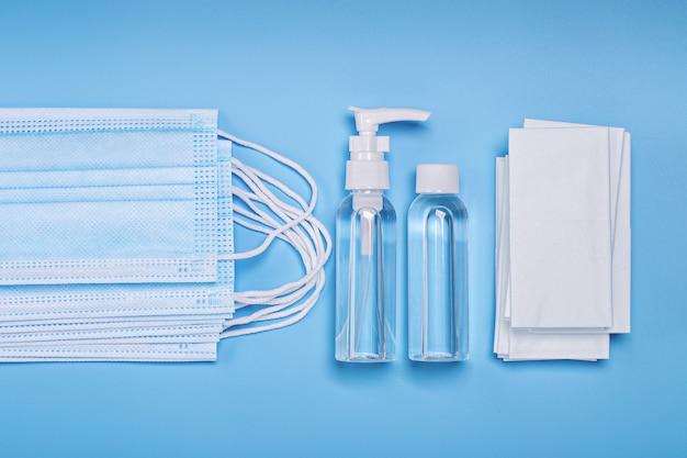 Бутылки с дезинфицирующим средством для рук, антибактериальные салфетки и маски для лица.