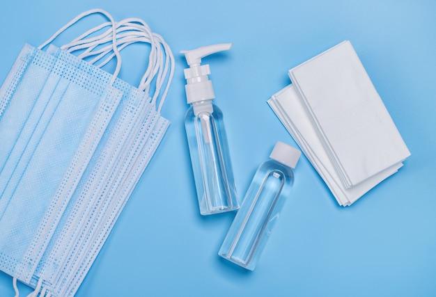 Бутылки с дезинфицирующим средством для рук, антибактериальные салфетки и медицинские маски для лица.