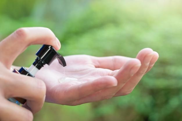 Дезинфицирующее средство для рук, крупным планом женские руки, используя моющее дезинфицирующее средство для рук, коронавирус