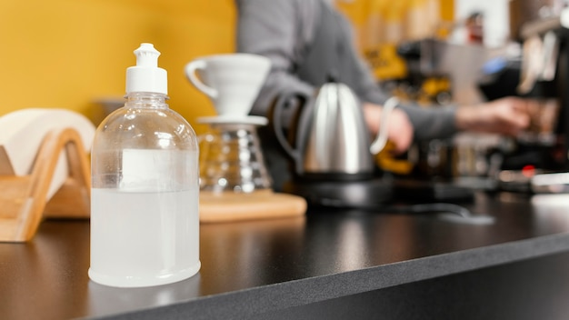 Hand sanitizer of the coffee shop counter with defocused male barista