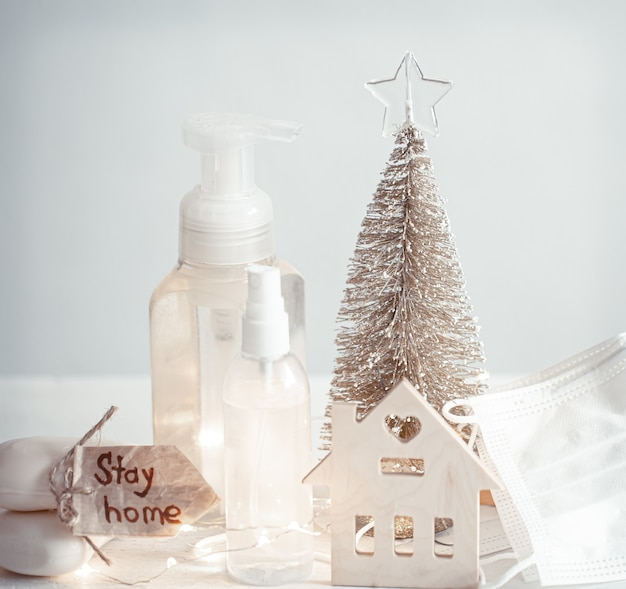 Hand sanitizer, disposable face masks, details of christmas decor on blurred light wall. christmas and coronavirus pandemic concept. covid-19.