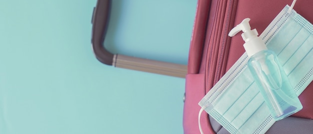 Hand sanitizer, face mask on red suitcase, reopen tourism, new normal for traveling concept