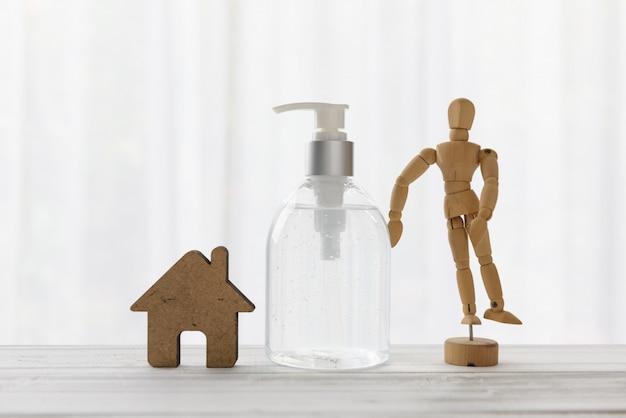 手の消毒剤、木製のテーブル上の家のアイコンcovid-19家庭検疫中。