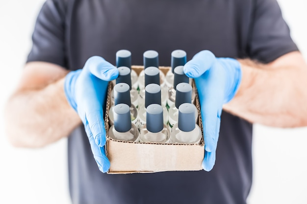 Hand sanitizer hygiene alcohol gel bottles in hands of man wearing latex medical gloves and protective mask during coronavirus covid-19 pandemics. healthcare hygiene and safety measures