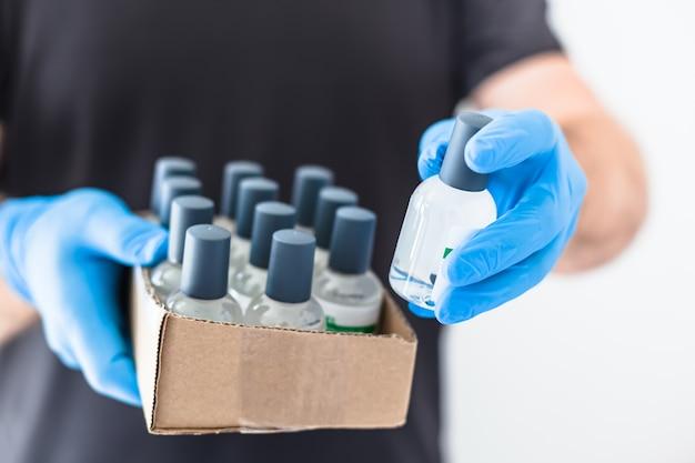 コロナウイルスcovid-19パンデミック時にラテックス医療用手袋と保護マスクを着用した男性の手に手指消毒剤衛生アルコールゲルボトル。ヘルスケアの衛生と安全対策