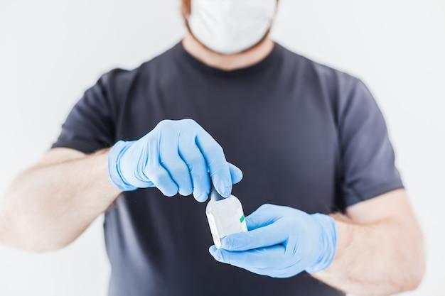 コロナウイルスcovid-19パンデミック中にラテックス医療用手袋と保護マスクを着用している男性の手に手指消毒剤衛生アルコールゲルボトル。ヘルスケアの衛生と安全対策