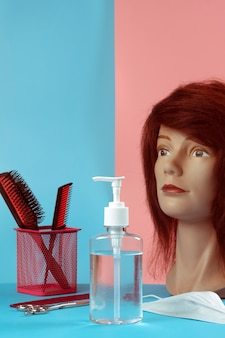 Hand sanitizer on a pink and blue surface and hairdressing set with a mannequin
