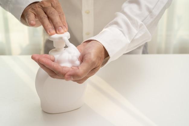 手の消毒剤の石鹸の泡は、コロナウイルスの発生を予防します。抗菌消毒石鹸のボトルを使用している人。 covid-19