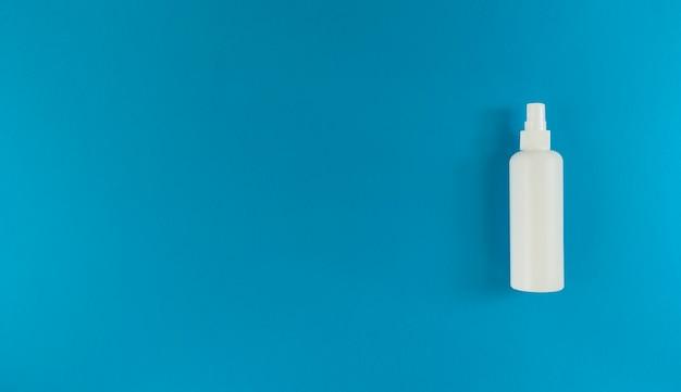 青い表面の右側にスプレーキャップ付きの手指消毒剤の白いボトル。コピースペースのあるシンプルなフラットレイ。医療の概念。