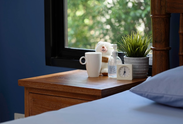 Hand sanitizer,white cup,teddy bear and alarm clock on wood table in blue bedroom