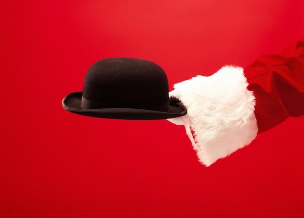 La mano di babbo natale che tiene un cappello nero su fondo rosso