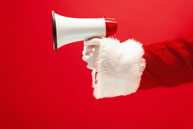 The hand of santa claus holding a megaphone on red