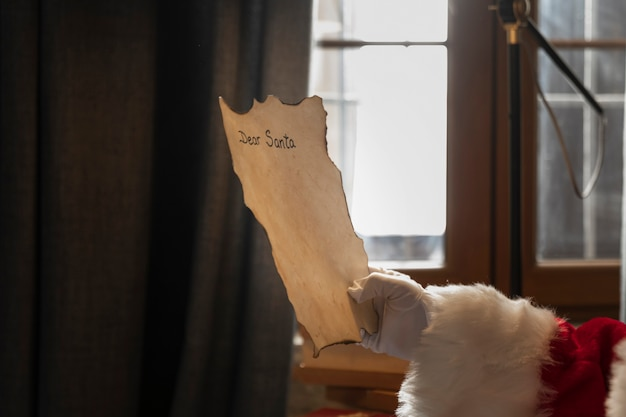 Hand of santa holding a letter addressed to him