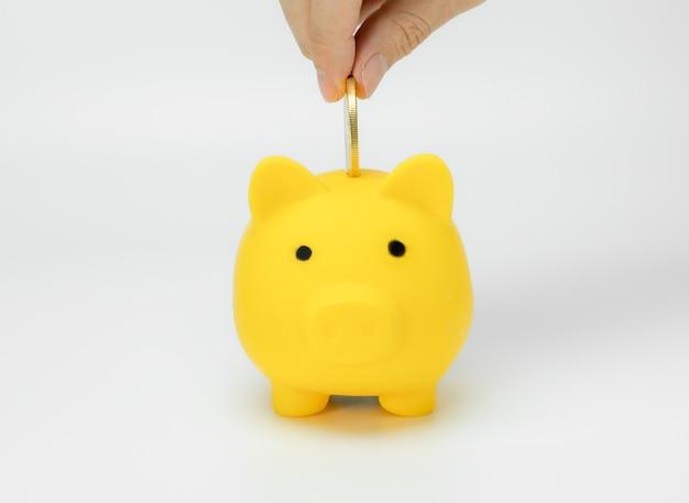 Hand saving money in piggy bank