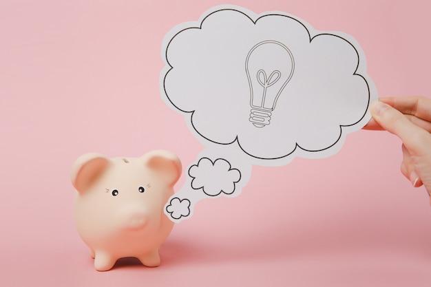 손으로 전구가 있는 구름, 파스텔 핑크색 벽 배경에 격리된 돼지 저금통 근처의 아이디어를 말합니다. 돈 축적, 투자, 은행 서비스, 부 개념. 공간 광고를 조롱하십시오.