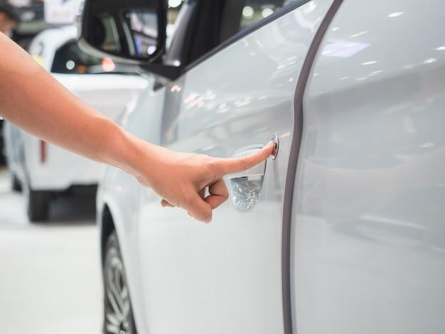 Ручное сканирование двери автомобиля белого цвета и концепция автосалона с размытием