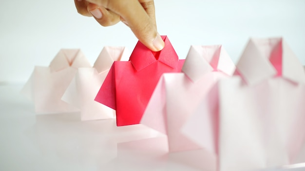 Hand selecting one red among white origami shirt paper