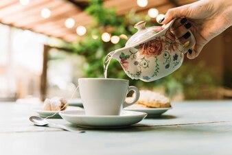 Hand serving tea