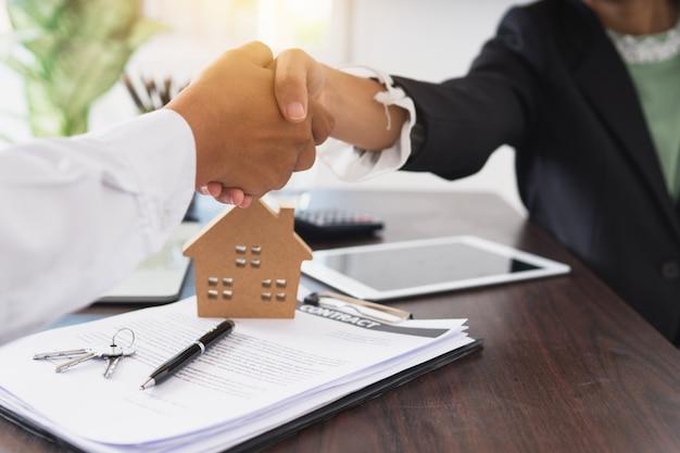 Рукопожатие агента по недвижимости с клиентом после подписания контракта в офисе банка, успешное соглашение и концепция договора купли-продажи дома