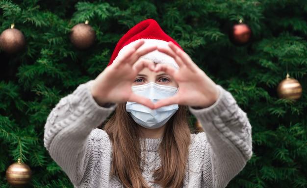 Сердце любви в форме руки. крупным планом портрет женщины в шляпе санта-клауса и медицинской маске с эмоциями. на фоне елки. коронавирус пандемия